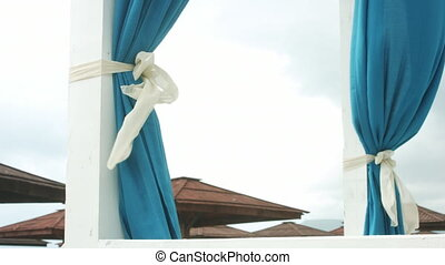 Blue curtains fluttering in the wind.