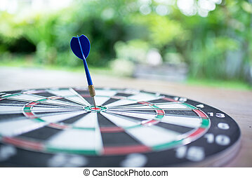 Blue dart arrow hitting in the target center of dartboard with green background