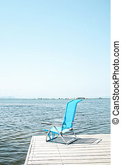 blue deck chair on a pier