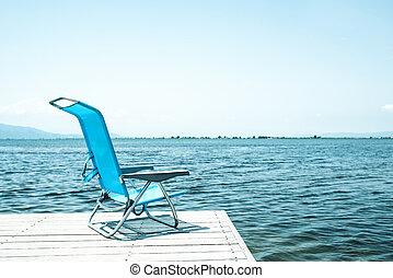 blue deck chair on a wooden pier