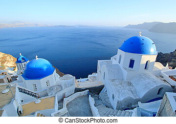 Famous Blue Domes of orthodox churches on the sea background in Santorini island, Greece.