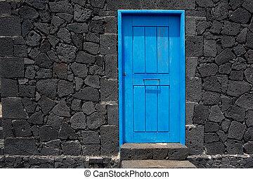 Blue door lava stone masonry wall at La Palma - Blue door in...