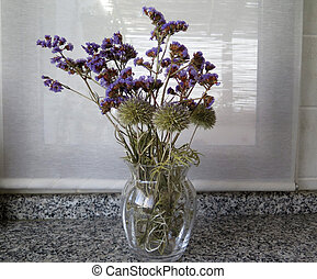 Blue dried wild flowers in glass vase on marble worktop