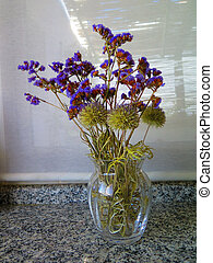 Blue dried wild flowers in glass vase on marble worktop