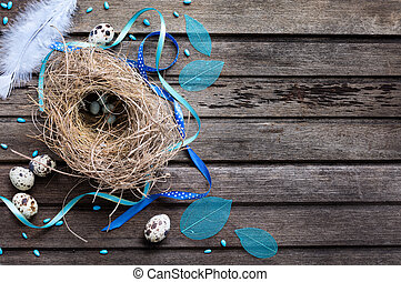 Blue Easter background with eggs in nest and decoratons on rustic wooden board