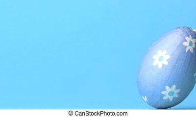 Blue easter egg rolling across blue - Blue wrapped easter...