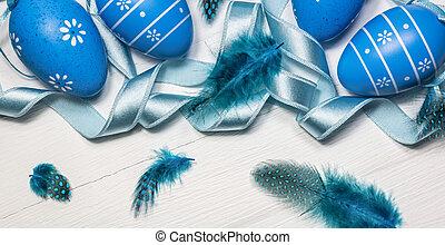Blue Easter eggs on white wooden background