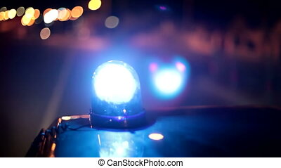 Blue emergency light on the roof of a police car riding down the street of the night city