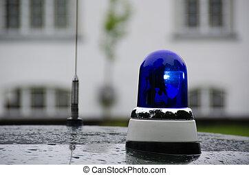 blue police light shining on an old police car in Denmark