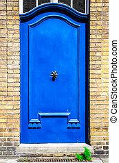 Blue entrance door in brick wall