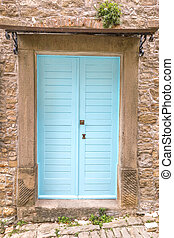 Blue entrance door to a house on stone street in Istria, Croatia, Europe.