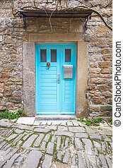 Blue entrance door with a mailbox to a house on stone street in Istria, Croatia, Europe.