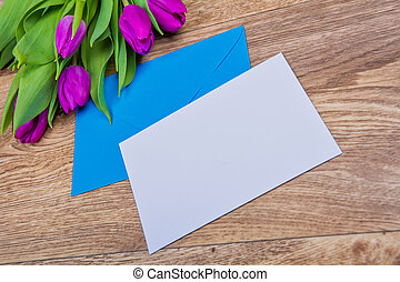 Blue envelope with tulips on a table