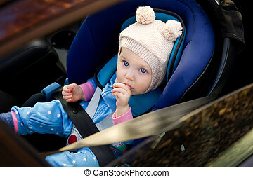 blue-eyed baby sitting in a car seat