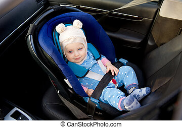 blue-eyed baby sitting in a car seat smiling, top view