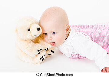 blue-eyed baby with a soft toy. studio photo. nausea. humor