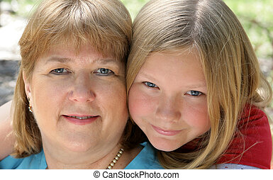 Closeup portrait of a pretty blond, blue-eyed mother and daughter.