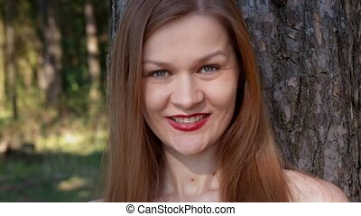Blue-eyed beautiful girl with red lips laughing, enjoying the nature.