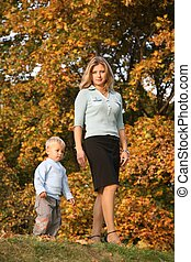 blue-eyed blond goes for a walk with the son in the park in autumn