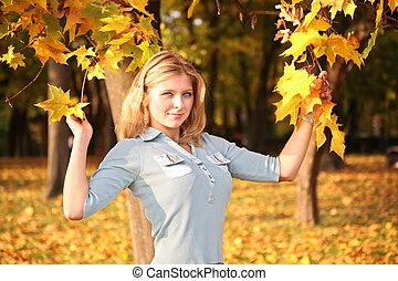 blue-eyed blond in the park in autumn with yellow leaves