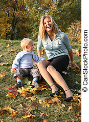 blue-eyed blond sits with the son in the park in autumn 2