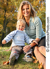 blue-eyed blond sits with the son in the park in autumn