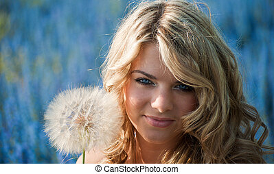 portrait of a blonde young woman with a big dandelion on a background of blue wild flowers. summer, outdoors.