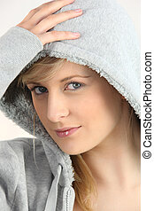 blue-eyed blonde wearing with hand on hood