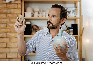 Blue-eyed ceramist working hard while performing order for...