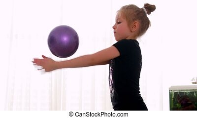 Blue-eyed girl Toddler does rhythmic gymnastics in a black bodysuit, plays with a ball on the home.