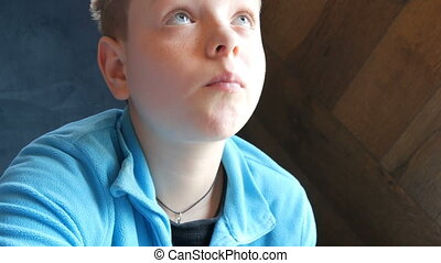 Blue-eyed handsome boy teen eats french fries in the fast...