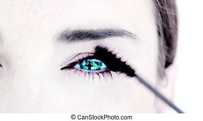 Blue eyed woman making up