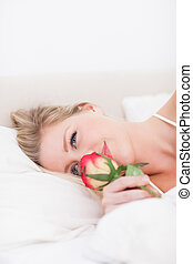 Blue eyed woman smelling a rose