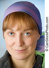 Portrait of adult woman in a bright headscarf. Look at the camera. Blue background. Closeup.