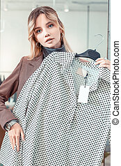 Blue-eyed young woman feeling amazing while shopping