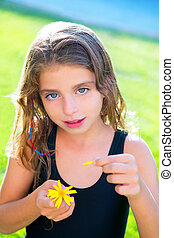 children girl testing love with yellow daisy flower petals