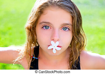 blue eyes kid girl with jasmine flower in mouth