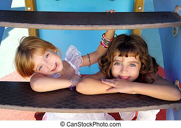 blue eyes little sister girls similing in playground stairs