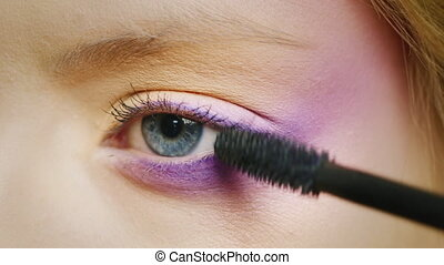 Blue eyes of a young woman - On eyelash mascara is applied,...