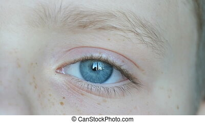 Blue eyes of blond boy teenager with red freckles on his...