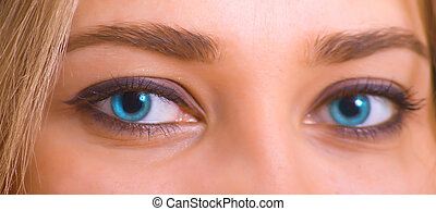Blue eyes of the young caucasian girl. Macro
