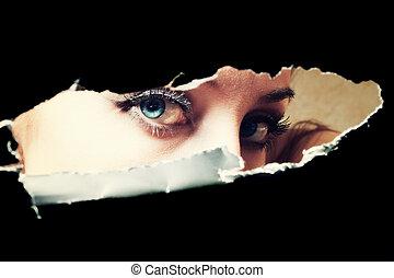 Blue eyes of young woman peeping through a hole closeup