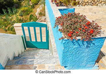 Blue fence and wall with red flowers, Greece