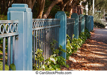 Blue Fence sidewalk - Blue metal and wood fence dimishing in...