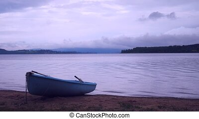 Blue fishing boat anchored on beach sand of lake. Smooth ...