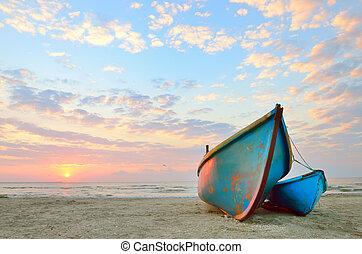 blue fishing boat at sunrise on black sea