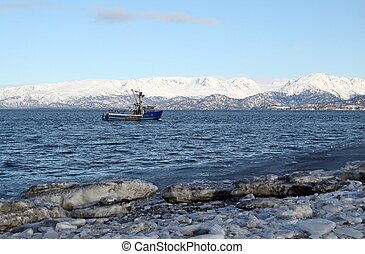 Blue fishing trawler heading out to sea