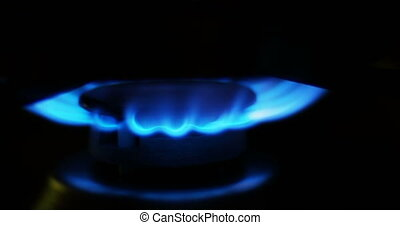 Blue flames of a gas in gas cooker. Fire on stove in dark.