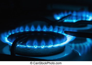 Blue flames of gas burning from a kitchen gas stove. Focus...