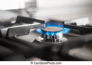 Blue flames of gas burning from a kitchen gas stove. Selective focus.